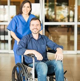 Man in wheelchair leaving hospital