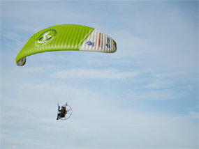 Sacha Dench flies in an electric paramotor set against a blue and wispy-cloudy sky