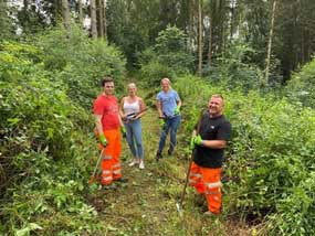 HPC workers and Stowey Green Spaces members posing for a photo after volunteering to clear a path through some local undergrowth